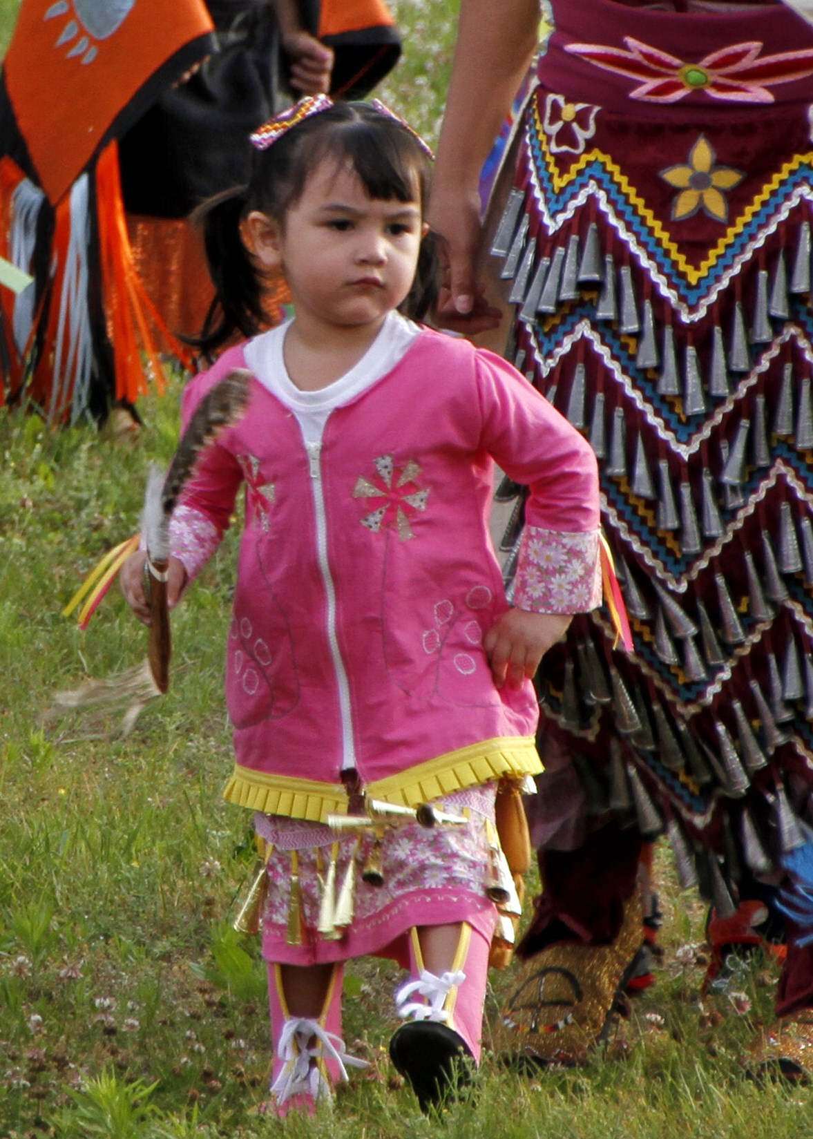 A young Ojibwe girl enjoys jingle-dress dancing. Some dresses include upwards of 200 jingles. In years past, the metal cones were often made from lids of snuff cans. (courtesy Dean Hall/Lakeland Times)