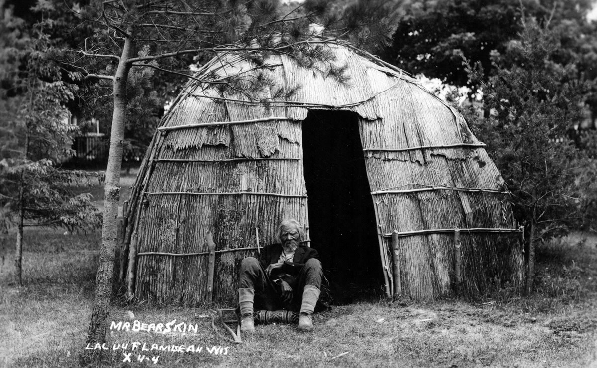 Lac du Flambeau medicine man Mr. Bearskin in front of an Ojibwe wigwam, early1900's. The top of the dome-shaped dwellings were covered with birch bark. A row of bulrush mats were tied around the sides, sometimes two rows for greater warmth. (Courtesy Wisconsin HistoricalSociety, #78915)