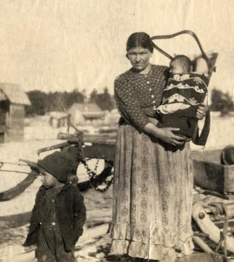 Ojibwe mother with children. The baby is in a traditional cradle board,<br /> secured by a decorative binding band. (Wisconsin Historical Society, WHS-23890.)